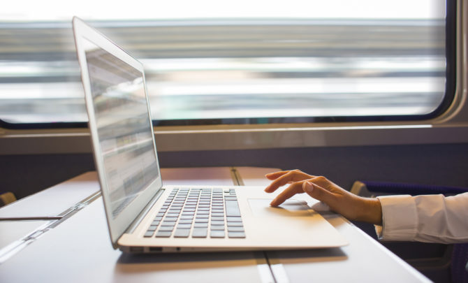 Woman hands typing on a laptop keyboard in the train