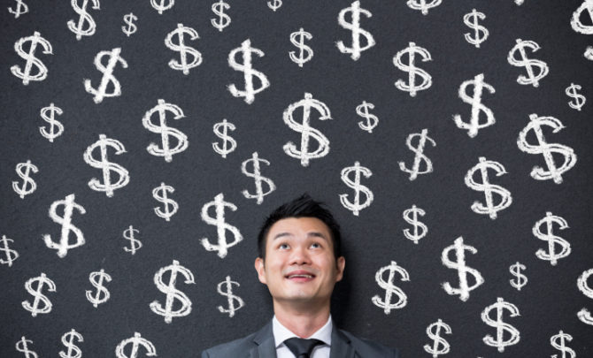 Chinese businessman in front of dollar signs written on wall.