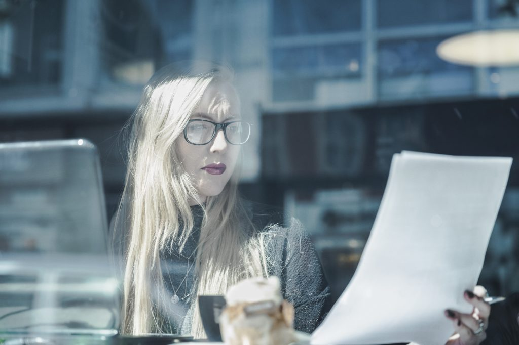 Businesswoman reading document in cafe