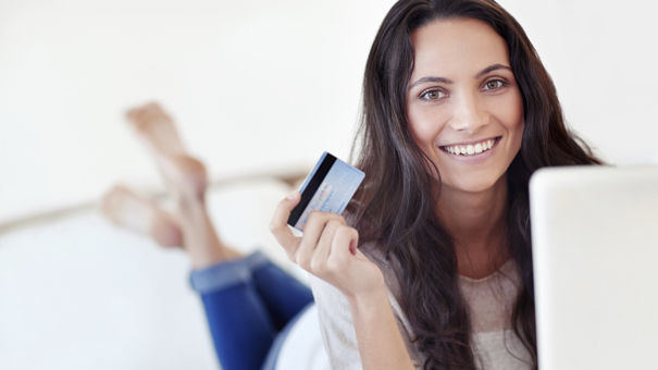 Portrait of a young woman holding a credit card while using a laptop